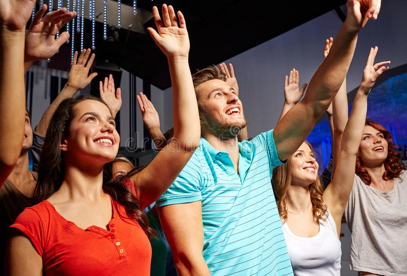 Smiling friends at concert in club. Party, holidays, celebration, nightlife and people concept - smiling friends waving hands at concert in club stock photo