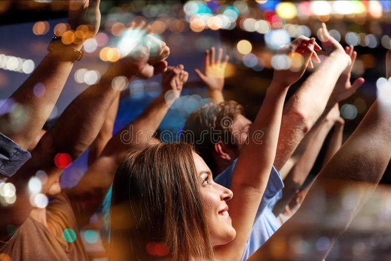 Smiling friends at concert in club. Party, holidays, celebration, nightlife and people concept - smiling friends waving hands at concert in club royalty free stock photography