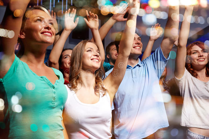Smiling friends at concert in club. Party, holidays, celebration, nightlife and people concept - smiling friends waving hands at concert in club stock image