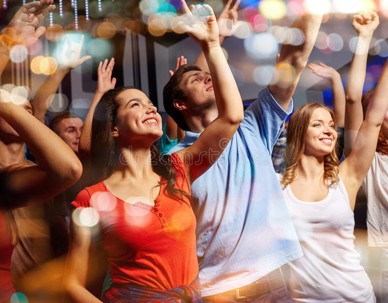 Smiling friends at concert in club. Party, holidays, celebration, nightlife and people concept - smiling friends waving hands at concert in club stock photography