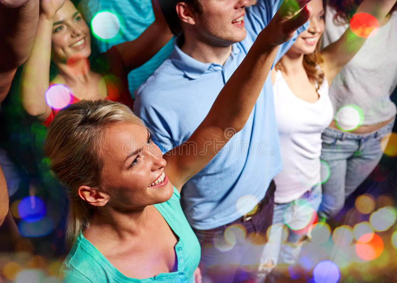 Smiling friends at concert in club. Party, holidays, celebration, nightlife and people concept - smiling friends waving hands at concert in club stock images