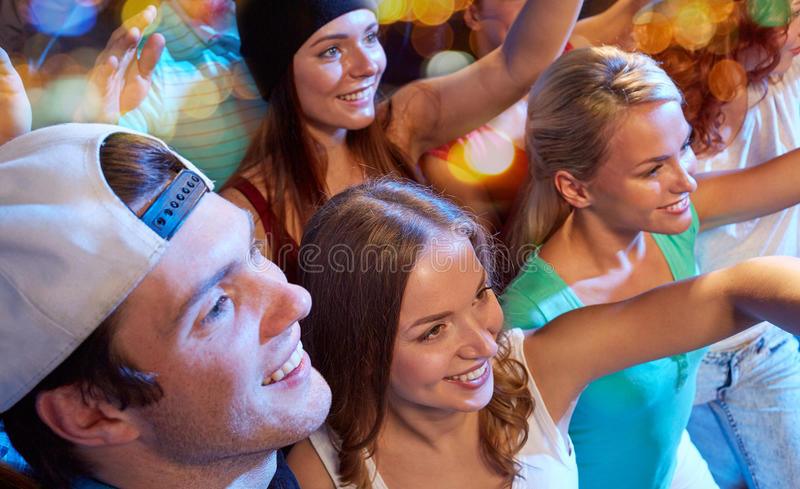 Smiling friends at concert in club. Party, holidays, celebration, nightlife and people concept - smiling friends waving hands at concert in club royalty free stock photos
