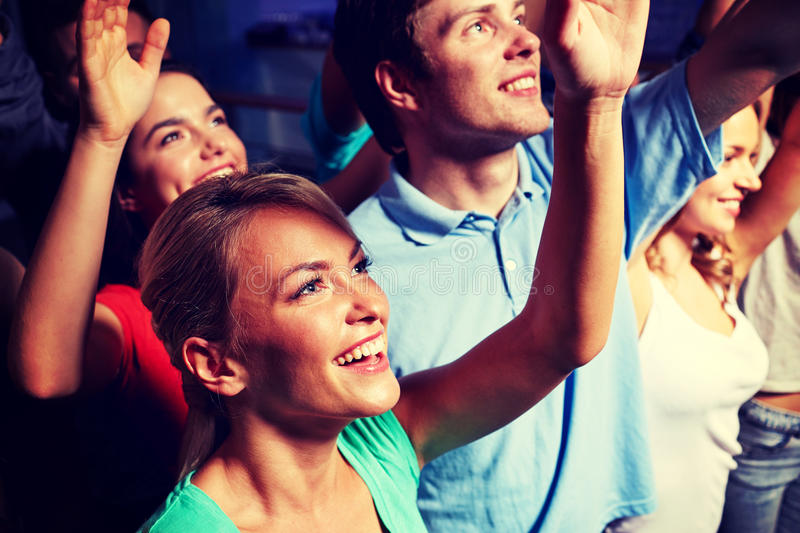 Smiling friends at concert in club. Party, holidays, celebration, nightlife and people concept - smiling friends waving hands at concert in club royalty free stock photo