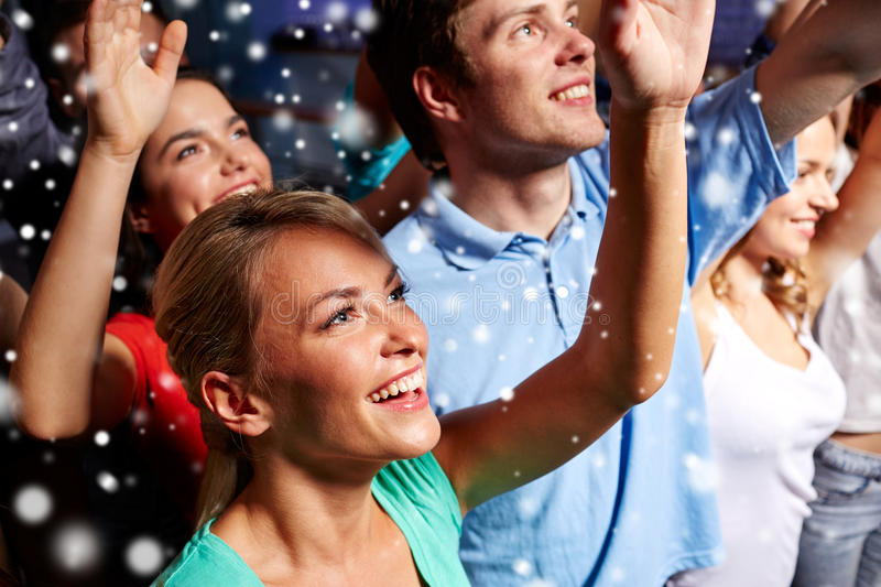 Smiling friends at concert in club. Party, holidays, celebration, nightlife and people concept - smiling friends waving hands at concert in club and snow effect royalty free stock images