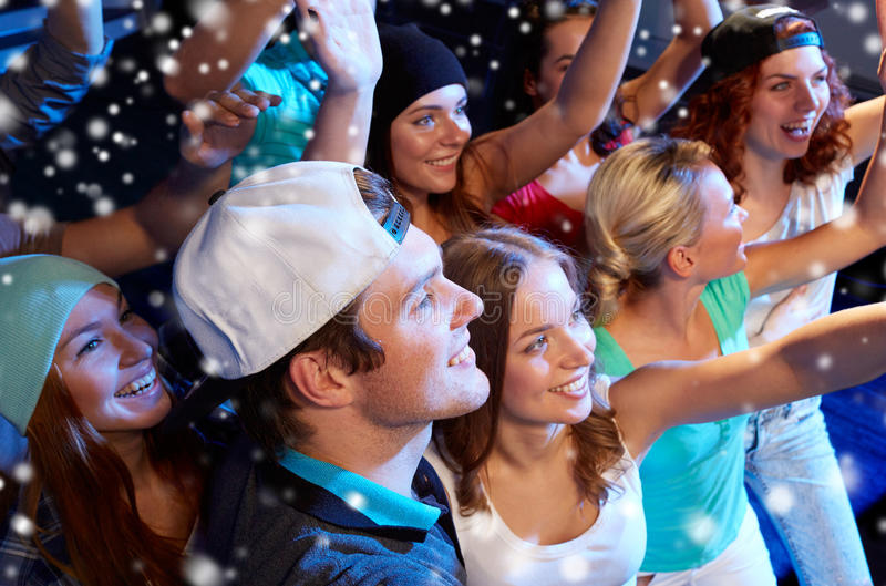 Smiling friends at concert in club. Party, holidays, celebration, nightlife and people concept - smiling friends waving hands at concert in club and snow effect royalty free stock photography