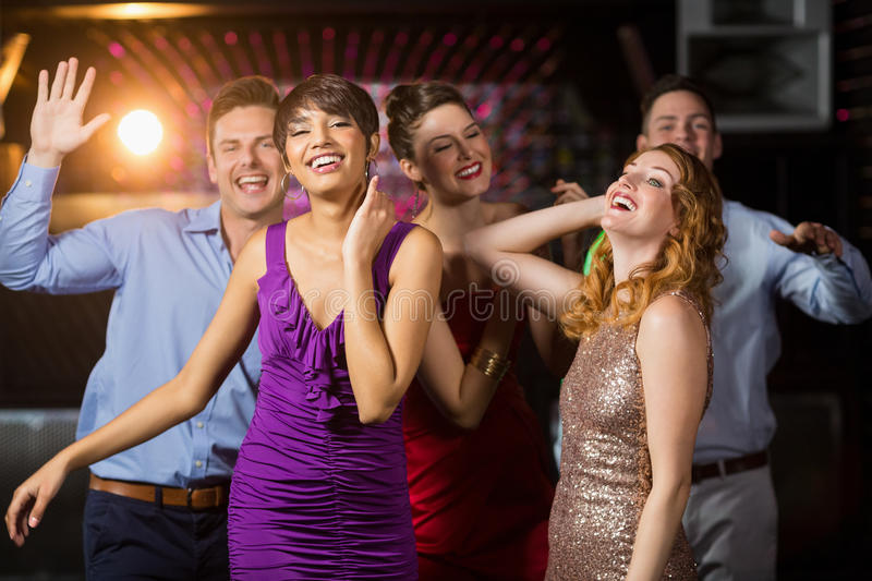 Smiling friends dancing on dance floor. Group of smiling friends dancing on dance floor in bar royalty free stock photography