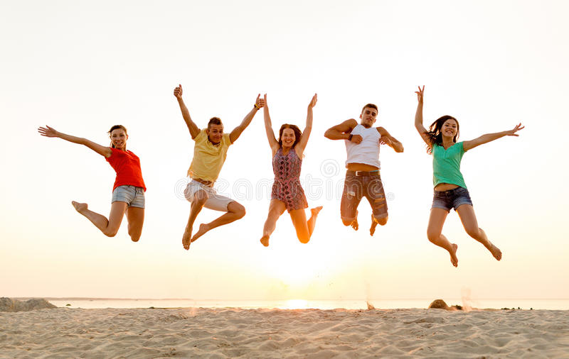 Download Smiling Friends Dancing And Jumping On Beach Stock Photo