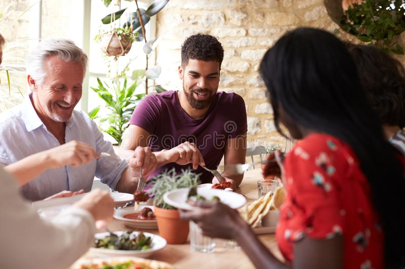Smiling friends eating together at a table in a cafe royalty free stock photo