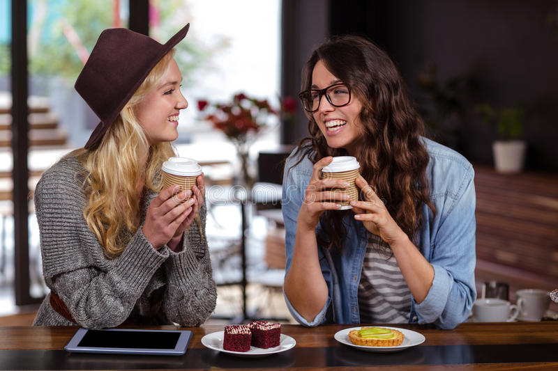 Smiling friends enjoying coffee and pastries royalty free stock images