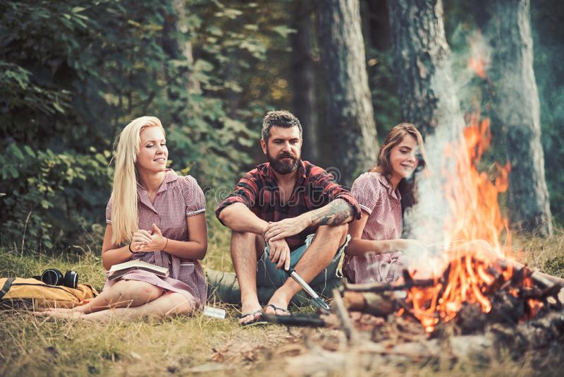 Smiling friends enjoying last summer days outdoors. Youngsters sitting around campfire. Girls reading books while royalty free stock image