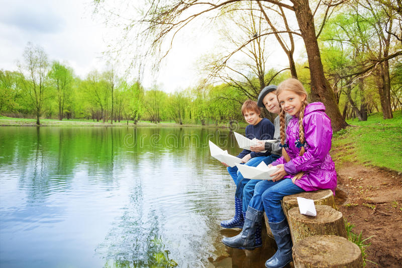 Smiling friends hold paper boats near river royalty free stock photo