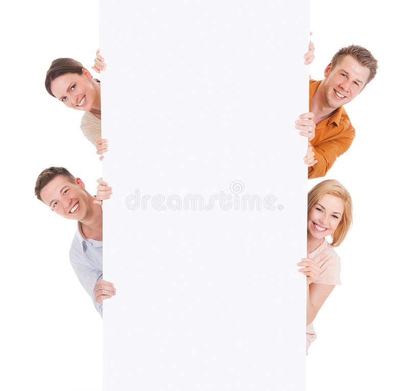 Smiling friends looking from behind the blank billboard stock image