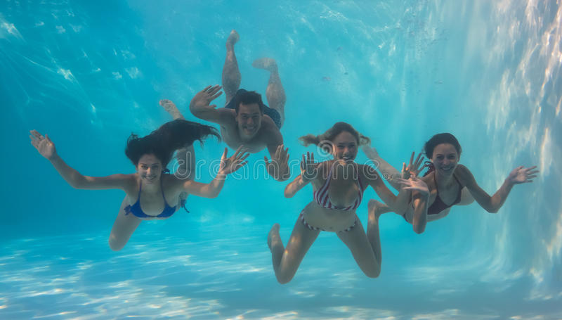 Smiling friends looking at camera underwater in swimming pool. On their holidays royalty free stock photos