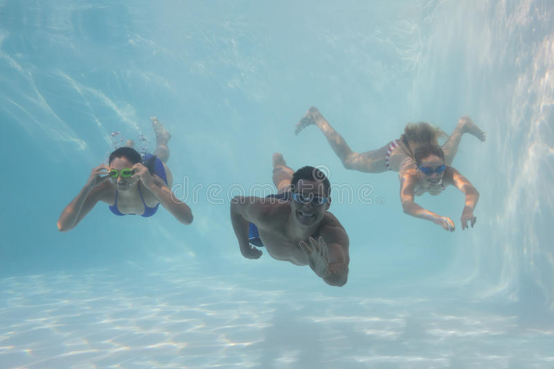 Smiling friends looking at camera underwater in swimming pool. On their holidays stock photo