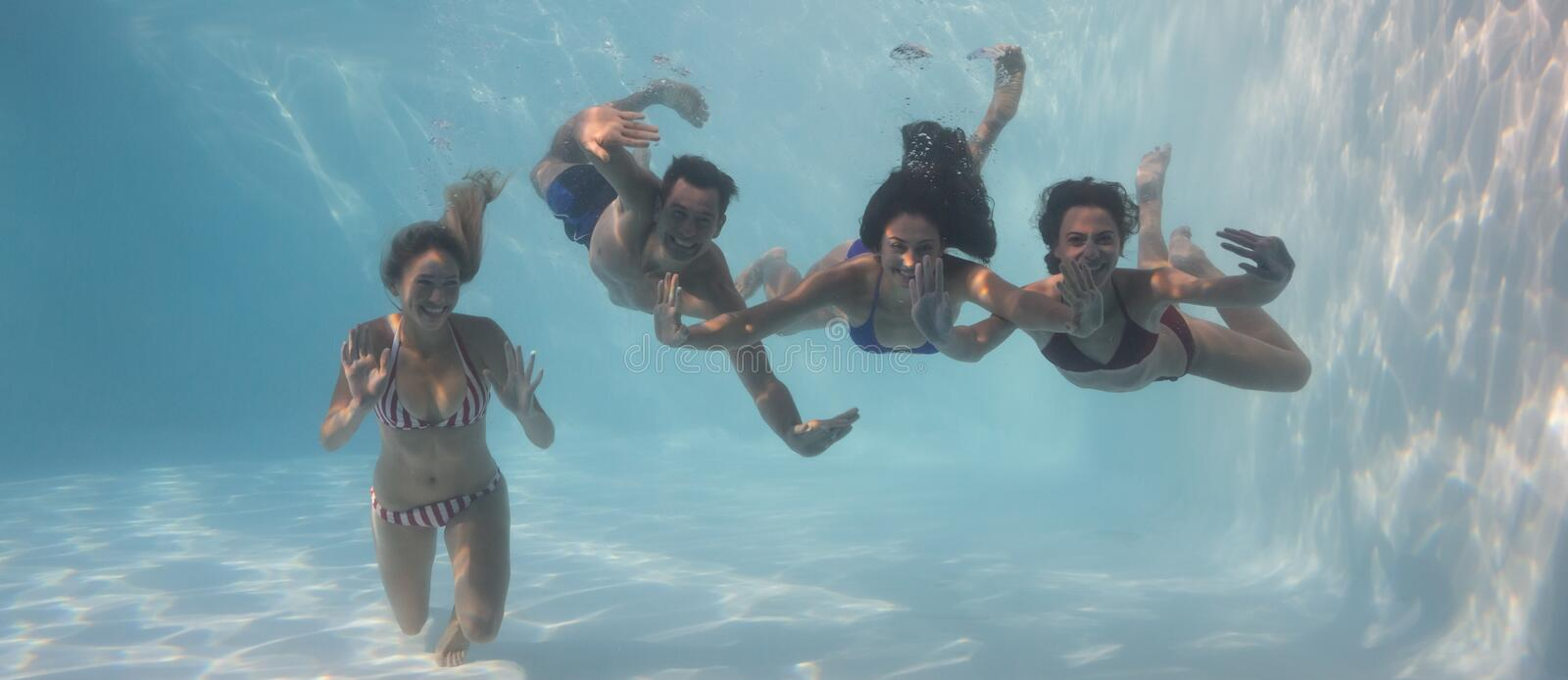 Smiling friends looking at camera underwater in swimming pool. On their holidays stock image