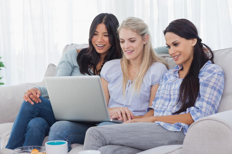 Download Smiling Friends Looking At Laptop Together Stock Photo - Image: 32515602