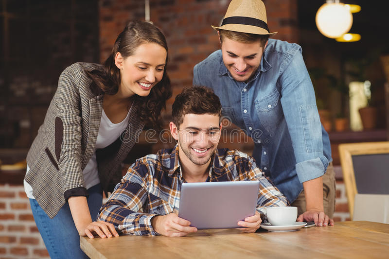 Smiling friends looking at tablet computer stock photo