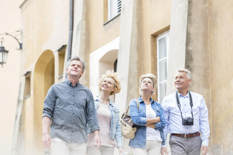 Smiling friends looking up while walking by building stock photo