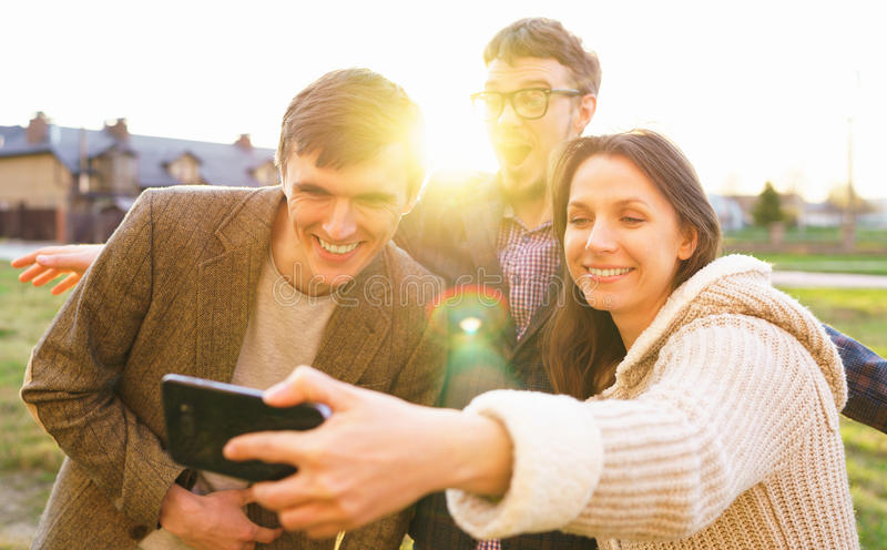 Smiling friends making selfie outdoors royalty free stock photos