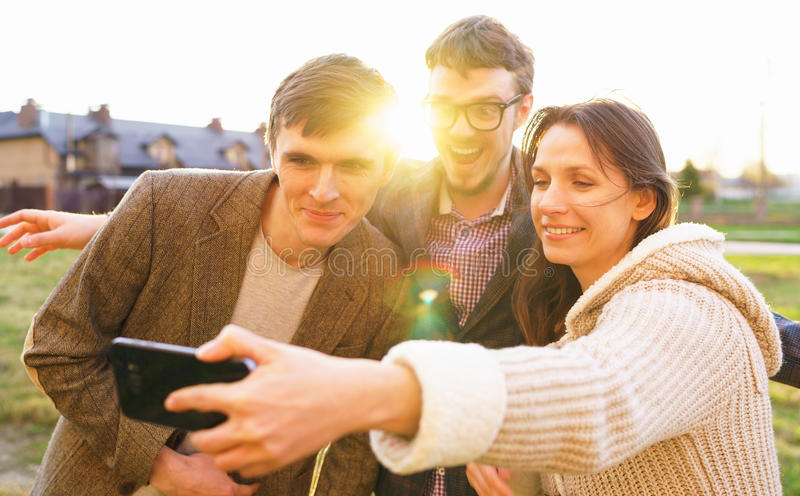Smiling friends making selfie outdoors stock images
