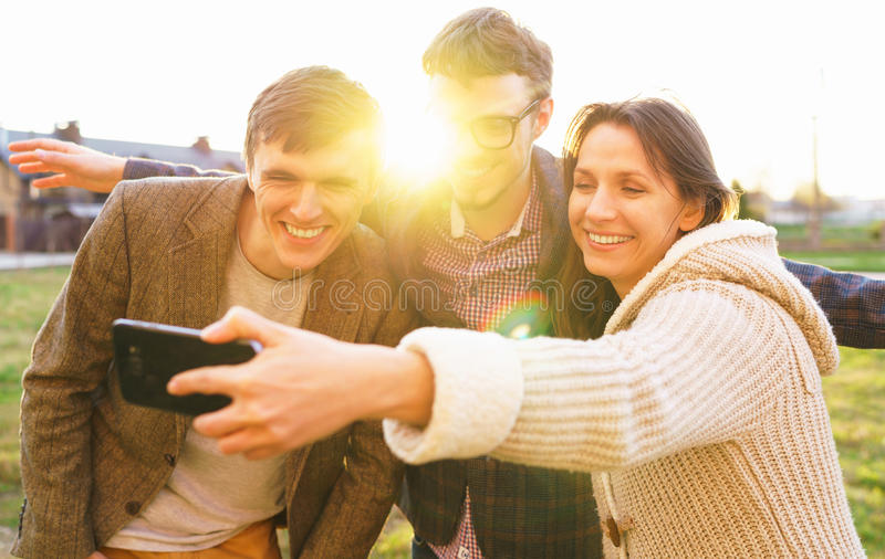 Smiling friends making selfie outdoors royalty free stock photo