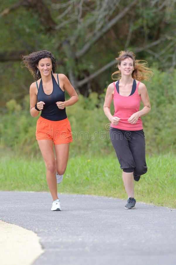 Smiling friends running outdoors royalty free stock photo