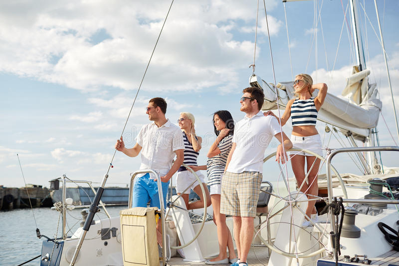 Smiling friends sailing on yacht. Vacation, travel, sea, friendship and people concept - smiling friends sailing on yacht royalty free stock photos