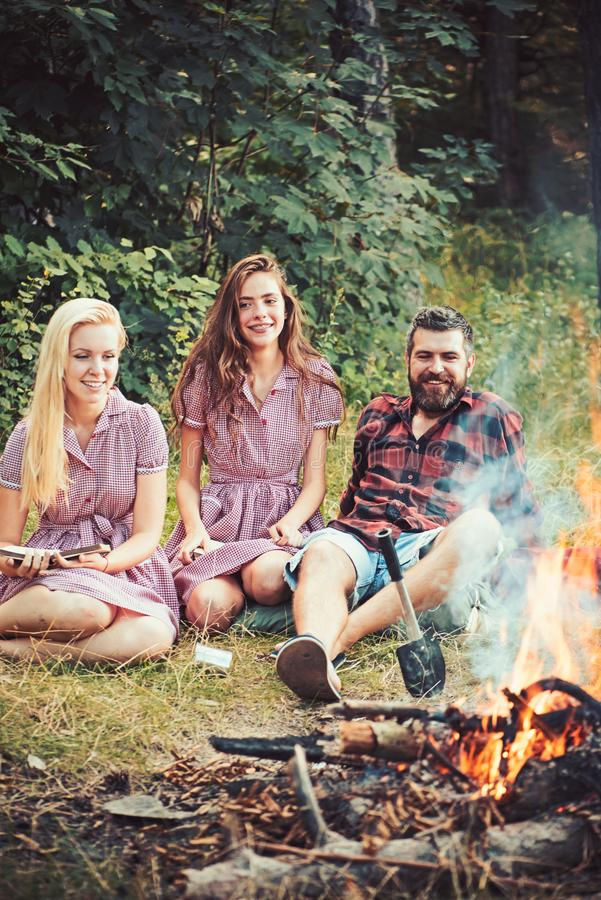 Smiling friends sitting next to campfire. Happy youngsters camping in forest. Bearded guy lying on grass while girls royalty free stock images