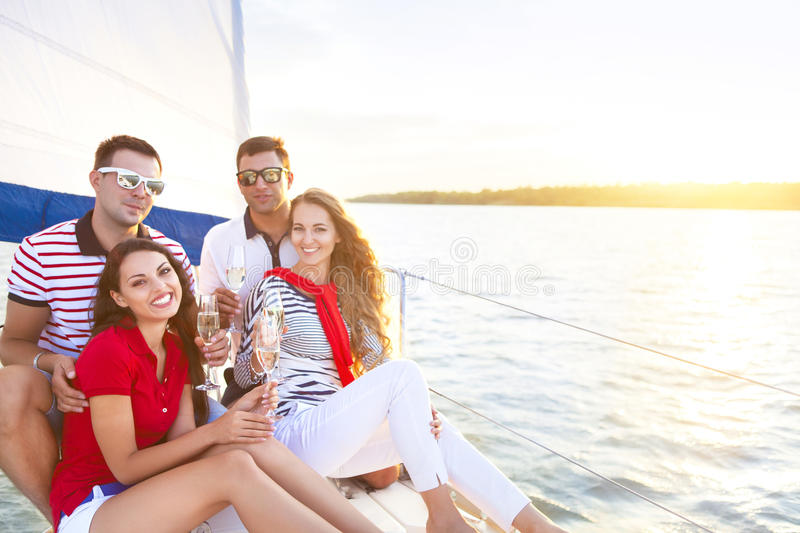 Smiling friends sitting on yacht deck and greeting drinking champagne stock images