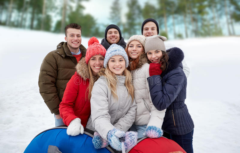 Smiling friends with snow tubes and selfie stick. Winter, leisure, friendship, technology and people concept - group of smiling young men and women with snow royalty free stock photos