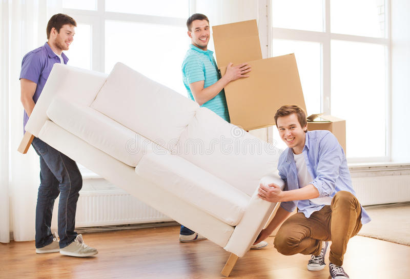 Smiling friends with sofa and cardboard boxes. Repair, furniture, decorating and home concept - smiling friends with sofa and cardboard boxes stock photo
