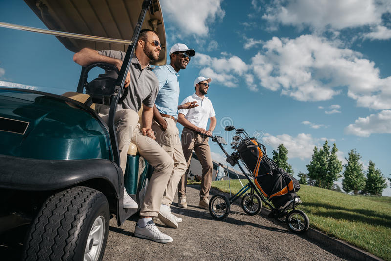 Smiling friends standing near golf cart and looking away stock image