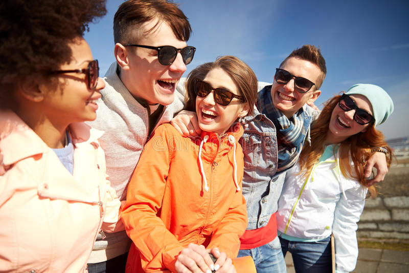 Smiling friends in sunglasses laughing on street. Tourism, travel, people, leisure and teenage concept - group of happy friends in sunglasses hugging and royalty free stock photo