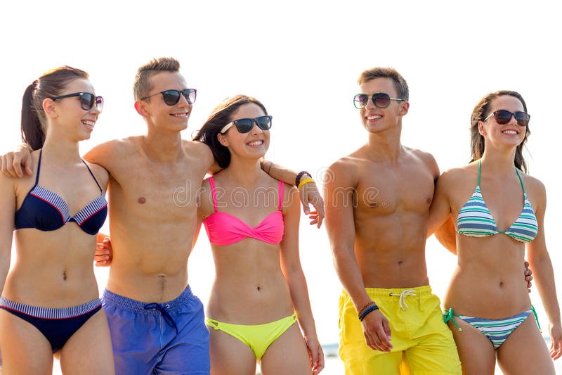 Smiling friends in sunglasses on summer beach stock images