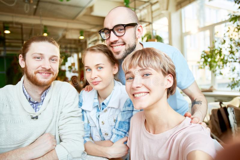 Smiling friends taking selfie in cafe royalty free stock photography