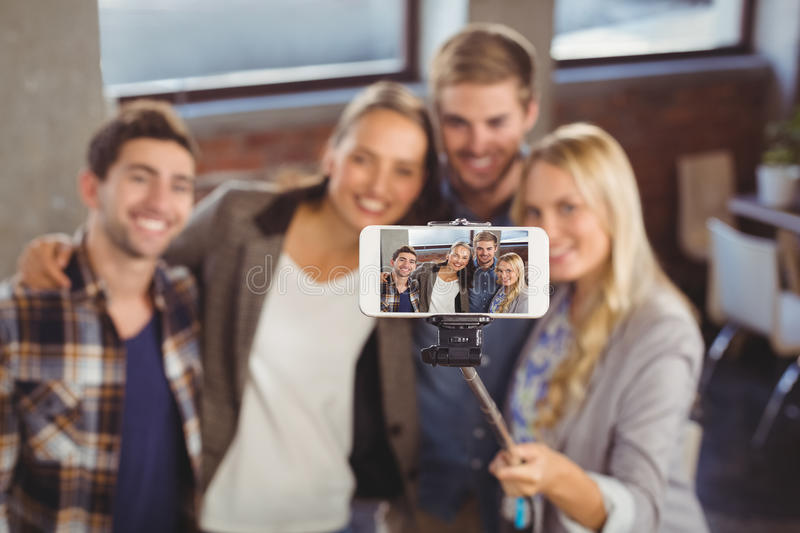 Smiling friends taking selfies with selfiestick stock photo
