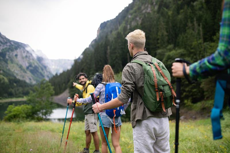 Smiling friends walking with backpacks. Adventure, travel, tourism, hike and people concept. royalty free stock images