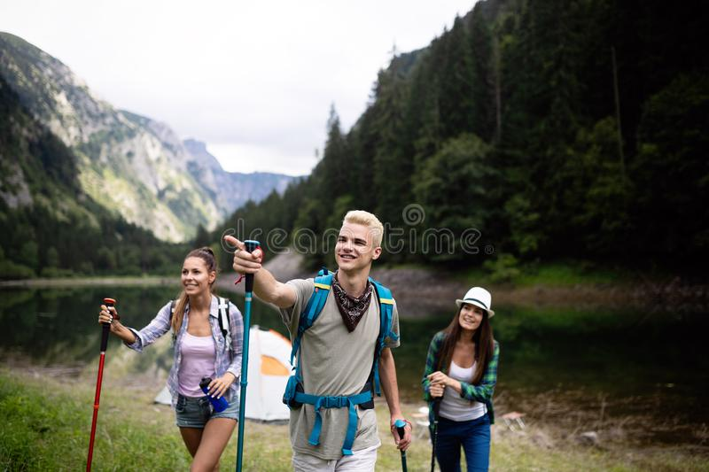 Smiling friends walking with backpacks. Adventure, travel, tourism, hike and people concept. royalty free stock photos
