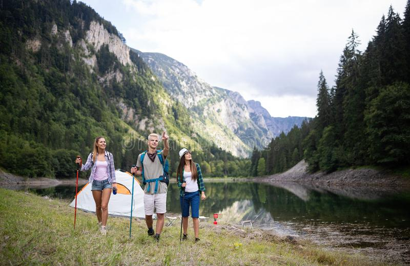 Smiling friends walking with backpacks. Adventure, travel, tourism, hike and people concept. stock image