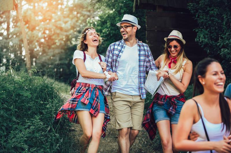 Smiling friends walking with backpacks in woods - adventure, travel, tourism, hike and people concept royalty free stock photo