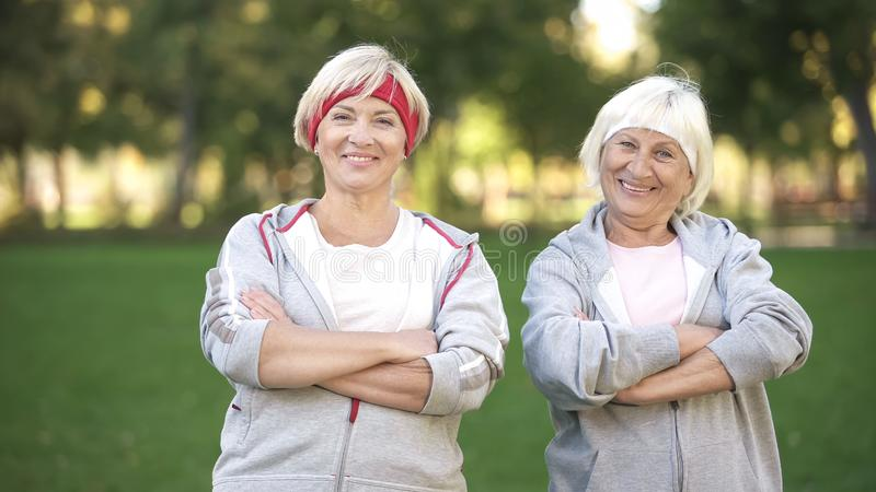 Smiling full of energy mature women posing in park after workout, fitness stock images