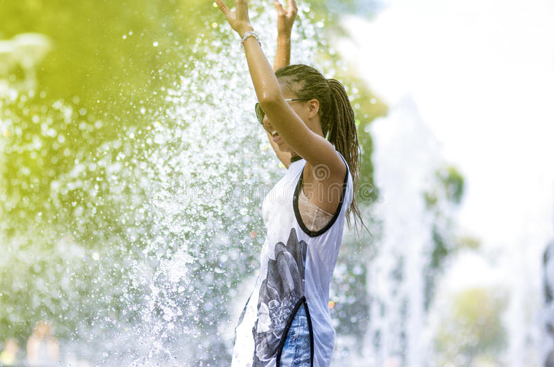 Smiling Funny African American Teenager Girl with Dreadlocks Enjoying in Fountain. Teenager Concepts. Portrait of Smiling Funny African American Teenager Girl stock photography