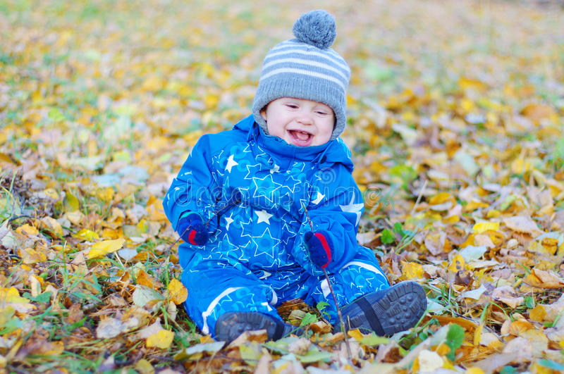 Smiling funny baby boy sitting on yellow leaves in autumn stock photography