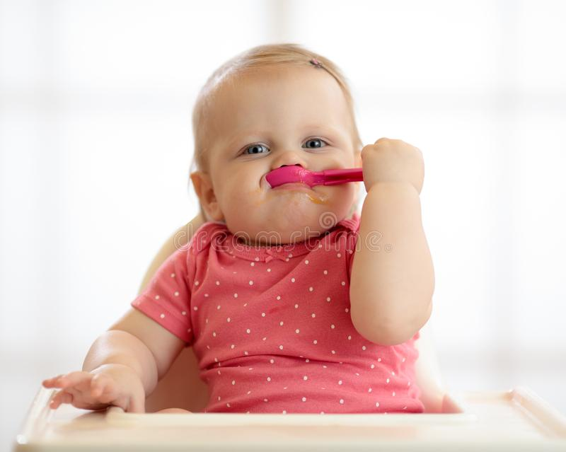 Smiling funny baby eating food alone. Smiling funny baby eating healthy food alone stock image