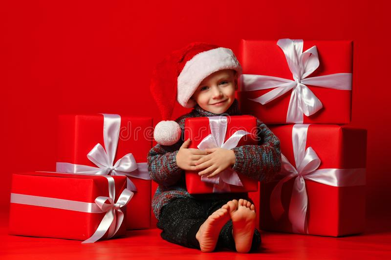Smiling funny child boy in Santa red hat fell asleep with Christmas gifts in hand in hand on red background. stock photography