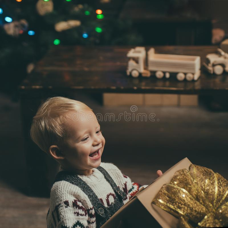 Smiling funny child in Santa hat holding Christmas gift in hand. Cute Baby, Merry Christmas. Merry christmas and Happy royalty free stock photo
