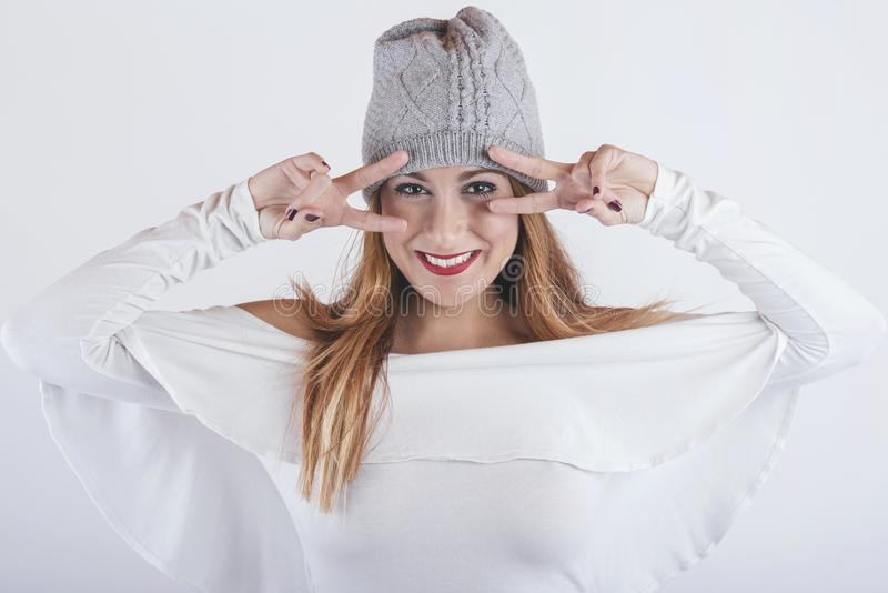 Smiling and funny girl with winter hat. On white background royalty free stock photo