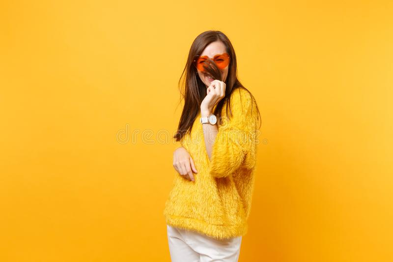 Smiling funny young woman in fur sweater and heart orange glasses holding, covering face with hair isolated on bright. Yellow background. People sincere royalty free stock photo