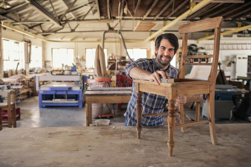 Smiling furniture maker sanding a chair in his woodworking shop. Smiling furniture maker sanding a wooden chair on a workbench while working alone in his large royalty free stock photo