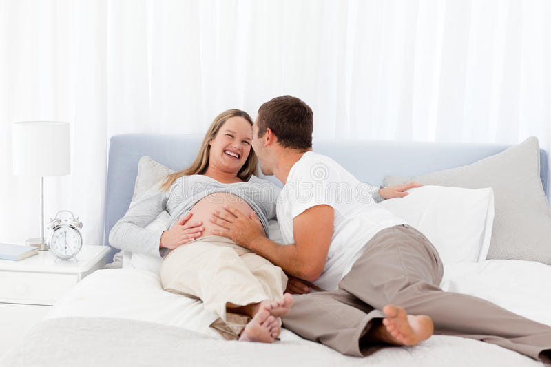 Smiling future parents liyng on the bed stock photos